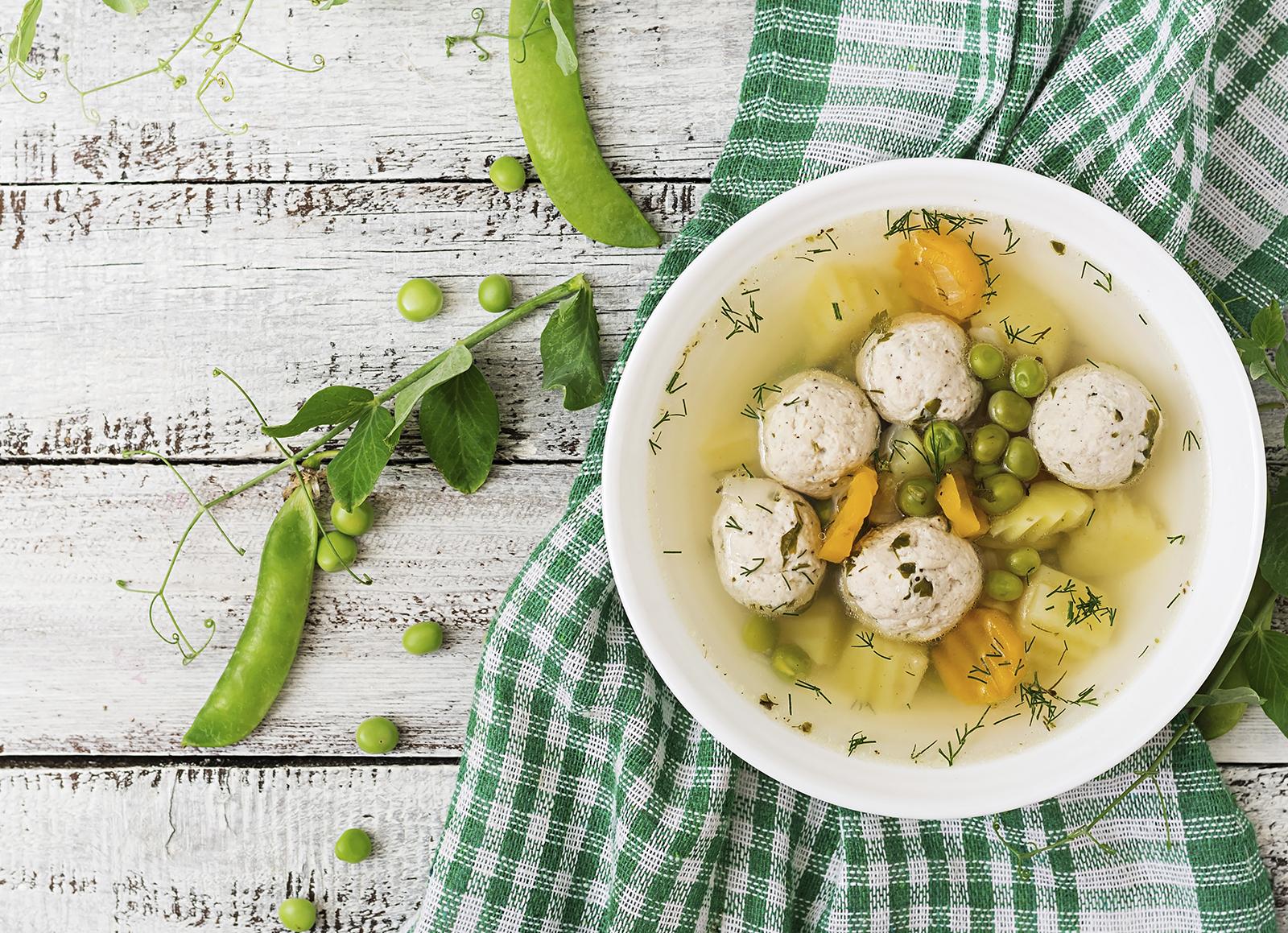 Sopa dietética con albóndigas de pollo, guisantes, zanahoria y patatas.